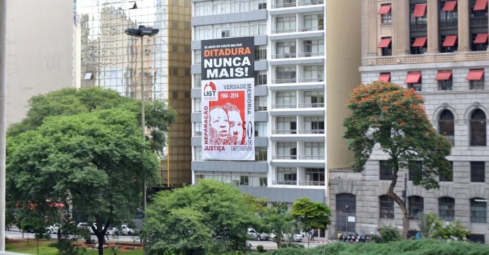 4.abr.2014 - Banner contra a Ditadura Militar e lembrando os 50 anos do golpe de 64, é pendurado e ocupa 5 andares do prédio do Sindicato dos Comerciários do Estado de São Paulo, na região do Vale do Anhangabaú, em São Paulo