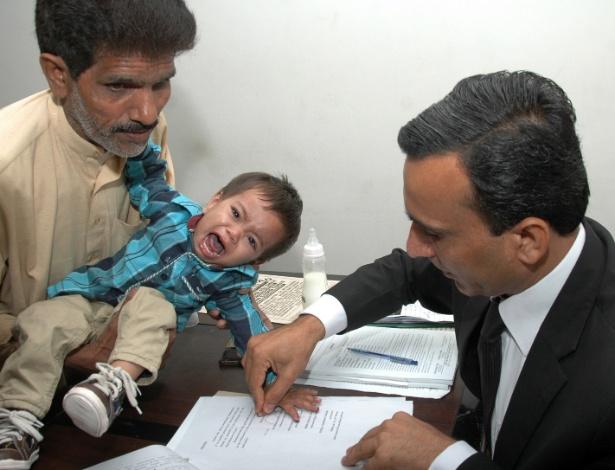5.abr.2014 - Foto tirada em 3 de abril mostra um policial paquistanês pegando as digitais do bebê Muhammad Mosa, que tem nove meses de vida. Ele foi acusado de tentativa de assassinato durante uma operação da polícia