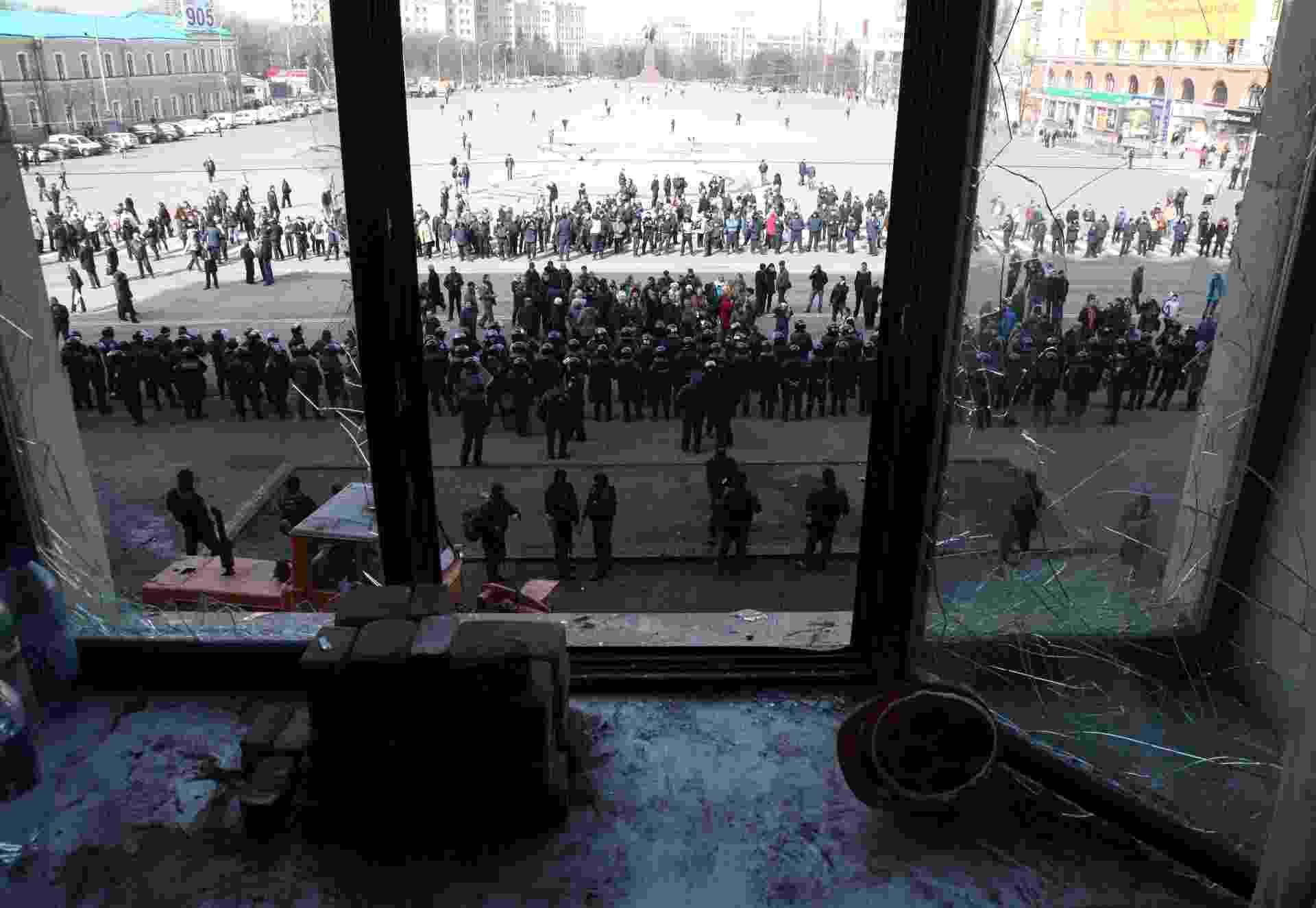 """8.abr.2014 - Trabalhadores limpam barricada enquanto policiais ucranianos guardam o edifício da administração pública da província de Kharkiv, leste da Ucrânia, nesta terça-feira (8). Policiais ucranianos ficaram feridos no decorrer de operação para libertar o prédio, ocupado por separatistas pró-Rússia. O presidente em exercício da Ucrânia disse que trataria separatistas que tomaram prédios no leste do país como """"terroristas? - Anatoliy Stepanov/AFP"""