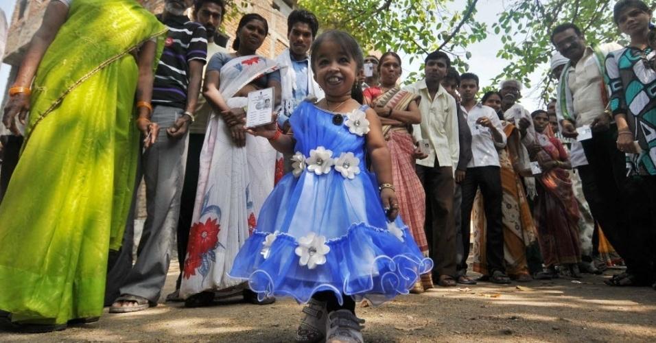 10.abr.2014 - Jyoti Amge, 20, mostra seu título de eleitor durante a sua chegada a uma sessão de votação na cidade de Nagpur, no centro da Índia, nesta quinta-feira (10). Jyoti recebeu do Guinness World Records o título de menor mulher do mundo. Cerca de 815 milhões de pessoas registraram seu voto no maior processo eleitoral do mundo, número que excede a população da Europa