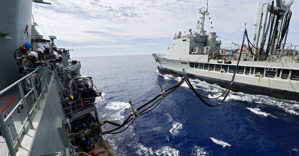 10.abr.2014 - Tripulação a bordo do navio da Marinha australiana HMAS Perth (à esquerda) acompanha reabastecimento no mar, feito por outro navio australiano, enquanto o Perth continua a procurar destroços do voo 370 da Malaysian Airlines. Estimativas da Reuters mostram que a busca pelo Boeing desaparecido desde 8 de março já custou pelo menos U$ 44 milhões (quase R$ 100 milhões) tornando-se a busca mais cara da história da aviação, com a contribuição de 26 países