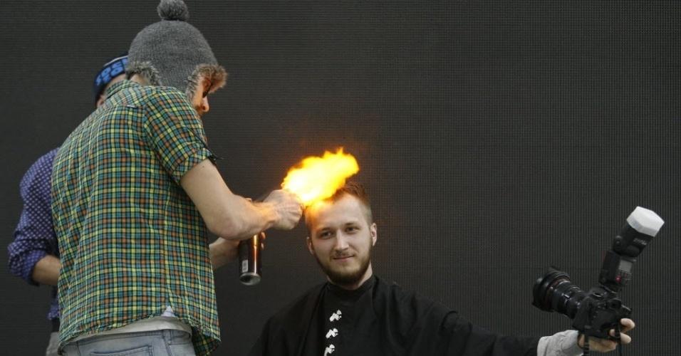 10.abr.2014 - Voluntário tira uma foto de si mesmo enquanto corta seu cabelo com um cabeleireiro que usa o fogo ao invés de tesouras no primeiro dia de um festival de primavera sobre beleza na cidade de Krasnoyarsk, na Rússia