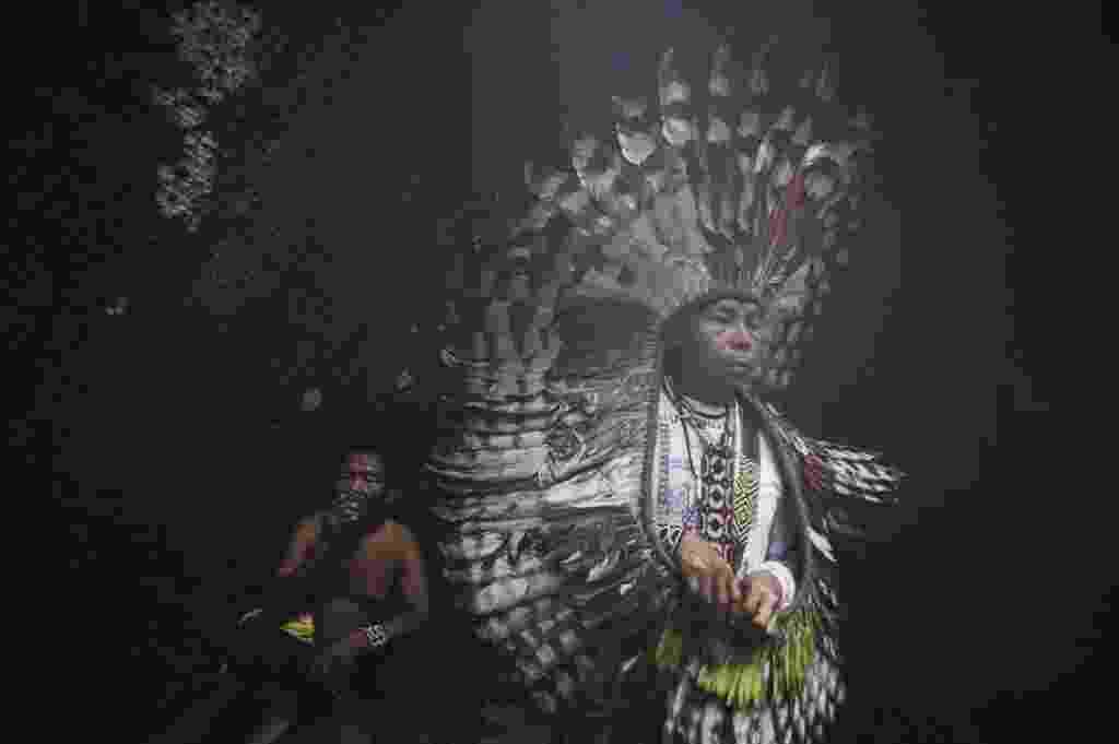 """9.mar.2014 - O líder espiritual da tribo huni kui participa de cerimônia em frente a uma árvore sumaúma sagrada (árvore que dá """"seda"""" e """"algodão"""") do lado de fora da aldeia Novo Segredo, ao longo do rio Envira, no Estado do Acre, em foto tirada em março deste ano. Moradores da porção da floresta tropical brasileira que fica próxima à fronteira com o Peru, os ashaninka e outros grupos indígenas, como os huni kui e madija, afirmam serem vítimas de usurpação de terras por tribos isoladas, definidas pela Survival International como grupos que nunca tiveram contato pacífico com a sociedade dominante. Os """"bravos"""", como esses indígenas são chamados na região, atacam outras aldeias, colocando as comunidades ao longo do rio Envira em alerta permanente, por isso os líderes dos ashaninka têm pedido ajuda ao governo e às ONGs a fim de não perderem as suas terras. Segundo eles, o movimento dessas outras tribos é o resultado da pressão causada pela exploração madeireira ilegal na fronteira com o Peru - Lunae Parracho/Reuters"""