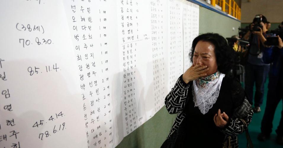 16.abr.2014 - A mãe de um passageiro que estava na balsa que afundou na Coreia do Sul descobre o nome do filho na lista de sobreviventes, nesta quarta-feira (16), em Jindo, onde estão reunidos os resgatados