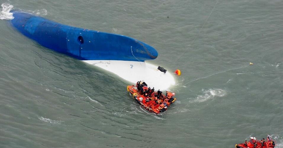 16.abr.2014 - Guarda Costeira sul-coreana busca sobreviventes junto a navio naufragado, instantes antes de a embarcação submergir por completo. Ao menos duas pessoas morreram e mais de 200 estão desaparecidas depois que o navio levando 476 passageiros afundou nesta quarta-feira (16)