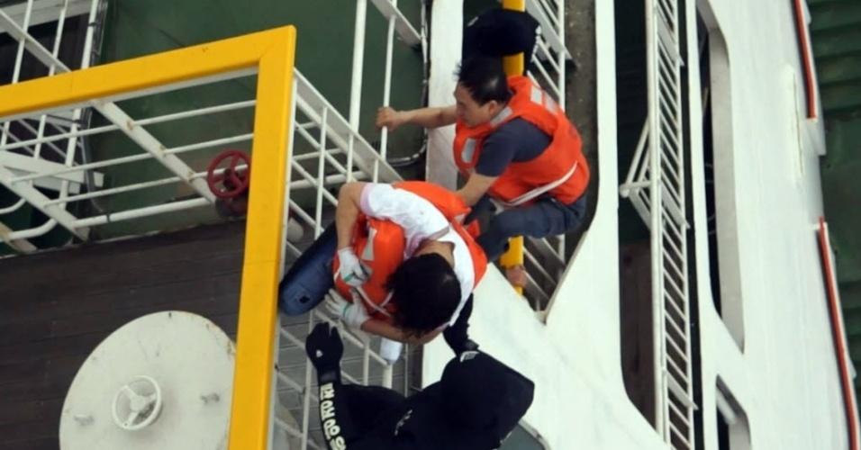 16.abr.2014 - Imagem cedida pela Guarda Costeira da Coreia do Sul mostra o resgate de passageiros (de laranja) de barca que naufragou no litoral de Jindo, na manhã desta quarta-feira (16). Uma embarcação que transportava 462 pessoas, a maioria estudantes do ensino médio, afundou no litoral do país. Pelo menos quatro morreram no acidente. A operação de resgate das vítimas envolve 34 barcos e 18 helicópteros