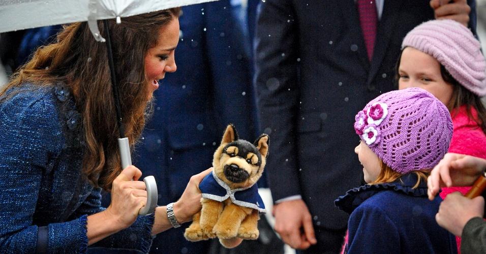 16.abr.2014 - Kate Middleton, a duquesa de Cambridge, recebe um cachorro de pelúcia de uma pequena moradora de Wellington, capital da Nova Zelândia, durante visita do casal real à Academia de Polícia do país, nesta quarta-feira (16). Kate, seu marido, o príncipe William, e o filho do casal, o príncipe George, estão em viagem de três semanas por Nova Zelândia e Austrália
