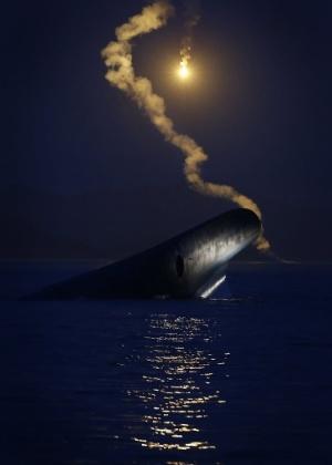 17.abr.2014 - Durante busca por passageiros desaparecidos no naufrágio da balsa na Coréia do Sul, policiais soltam fogos para iluminar o mar