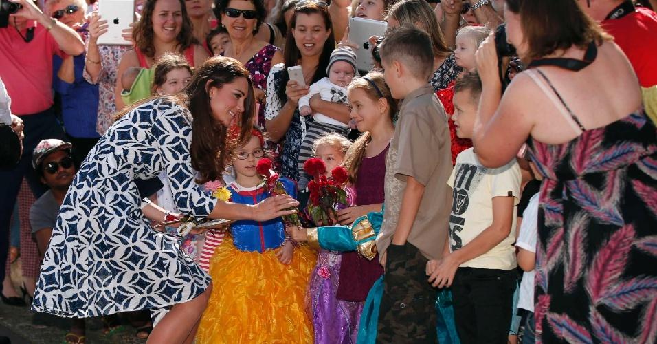 17.abr.2014 - Kate Middleton, a duquesa de Cambridge, recebe flor de uma menina durante visita às Blue Mountains, região da Austrália que foi atingida por incêndios florestais em outubro do ano passado