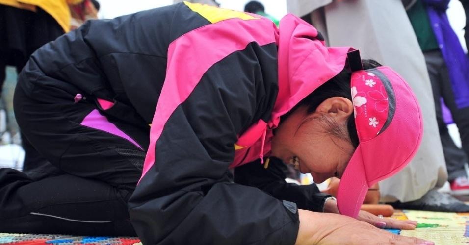 17.abr.2014 - Mulher reza por passageiros após o naufrágio de uma balsa na Coreia do Sul, nesta quinta-feira (17), horário de Brasília. Das 475 pessoas que estavam a bordo da embarcação e 179 foram resgatadas com vida