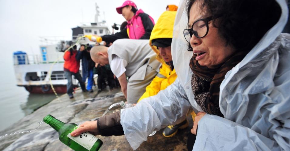 18.abr.2014 - Familiar joga álcool ao mar, enquanto reza pelos desaparecidos da balsa que virou e naufragou na costa de Jindo, no sul da Coreia do Sul. Equipes de resgate da Coréia do Sul, incluindo mergulhadores de elite da Marinha, correm contra o tempo para encontrar até 293 pessoas desaparecidas, em sua maioria alunos de ensino médio que faziam uma viagem de campo. Nesta sexta-feira os mergulhadores conseguiram entrar na embarcação pela primeira vez