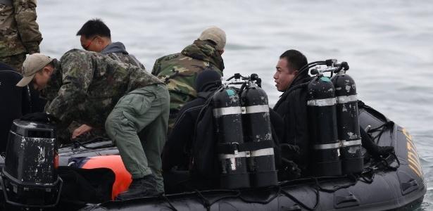 Equipes de mergulhadores da Marinha sul-coreana participam das buscas das vítimas do naufrágio da  balsa; apesar de localizar três corpos, eles não puderam ser resgatados por causa dos coletes salva-vidas - Kim Hong-Ji /Reuters