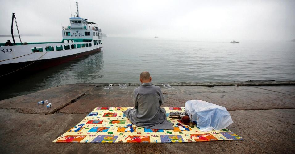 """18.abr.2014 - Monge budista reza para os passageiros desaparecidos que estavam na balsa sul-coreana """"Sewol"""", que afundou no mar a 20 km da costa, próximo a Jindo, onde familiares esperam notícias. O número de mortos no naufrágio aumentou para 25 nesta sexta-feira, e os pais dos mais de 300 alunos a bordo culpam o capitão do navio pela tragédia. Investigações apontam que um suboficial comandava a embarcação no momento que adernou, enquanto o capitão encontrava-se longe da ponte de comando"""
