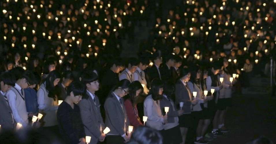 19.abr.2014 - Alunos da escola sul-coreana de ensino médio Danwon fazem uma vigília pelos colegas que estavam a bordo da balsa que naufragou em Jindo, Coreia do Sul. Familiares dos passageiros ofereceram amostras de DNA neste sábado (19) para ajudar na identificação dos mortos, enquanto o resgate se transformou em uma missão para recuperar a embarcação e os corpos das vítimas