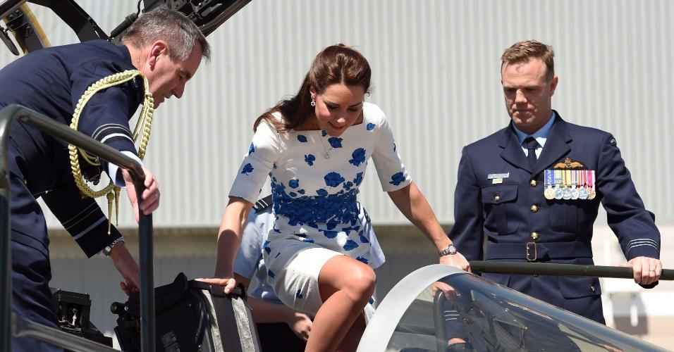 19.abr.2014 - Auxiliada por oficiais, Catherine, a Duquesa de Cambridge, entra no cockpit de um Super Hornet da Força Aérea australiana, na base de Amberley, leste da Austrália, neste sábado (19). O país é a segunda escala da viagem de 19 dias de Kate, o príncipe William e o filho do casal, o príncipe George, por Nova Zelândia e Austrália