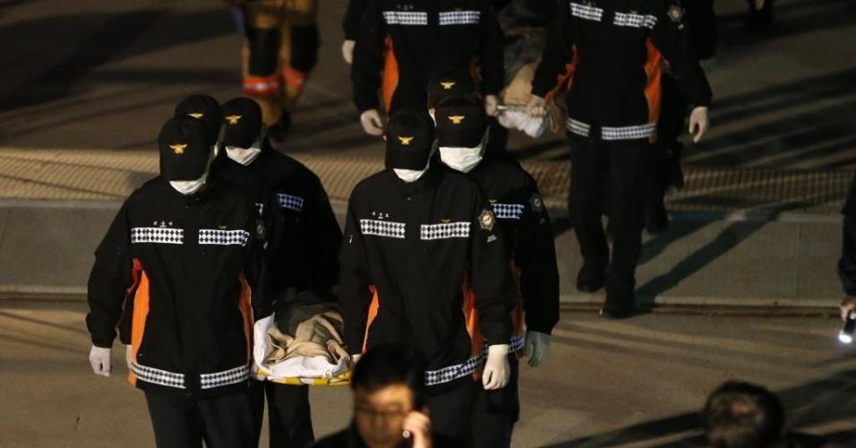 19.abr.2014 - Equipes de resgate da Coreia do Sul carregam corpos dos passageiros que estavam na balsa que naufragou na quarta-feira (16) no litoral do país. Familiares das vítimas ofereceram amostras de DNA neste sábado (19) para ajudar na identificação dos mortos