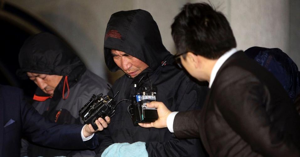 19.abr.2014 - Jornalistas questionam Lee Joon-seok, o capitão da balsa sul-coreana que afundou a 20 km da costa, após sua saída do tribunal, em Mopko, sul da Coreia do Sul. Lee, 69, foi preso neste sábado, respondendo a cinco acusações, incluindo negligência, acerca do naufrágio da balsa Sewol, que já causou ao menos 29 mortes entre os 475 a bordo. Ao menos 270 pessoas seguem desaparecidas