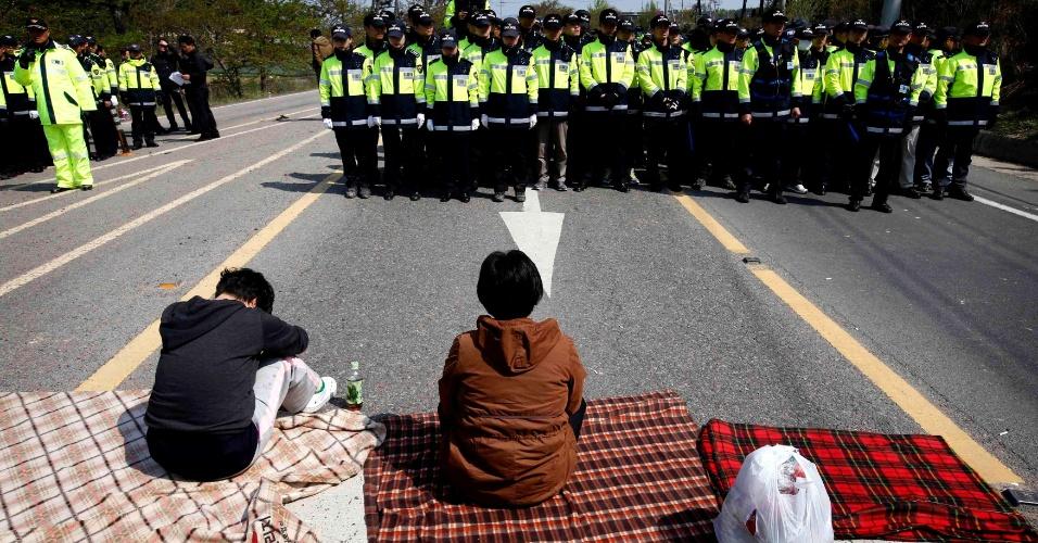 20.abr.2014 - Familiares de passageiros desaparecidos no naufrágio da balsa Sewol na costa da Coreia do Sul fecham estrada diante de bloqueio policial em Jindo, sul do país, durante um protesto exigindo uma reunião com o presidente Park Geun-hye. Parentes irritados das centenas de desaparecidos entraram em confronto com a polícia na manhã de domingo (20), enquanto mergulhadores retiravam mais corpos de dentro da embarcação, aumentando o número oficial de mortos para 49