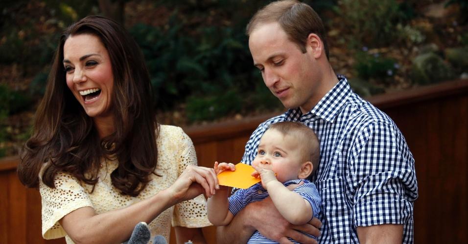 20.abr.2014 - Kate Middleton, a duquesa de Cambridge, ri do filho, o príncipe George, no colo do pai, o príncipe William,que morde um presente que foi dado a ele, durante uma visita ao zoológico Taronga, em Sidney, neste domingo (20). O casal real está em visita oficial de 19 dias à Nova Zelândia e Austrália com o filho