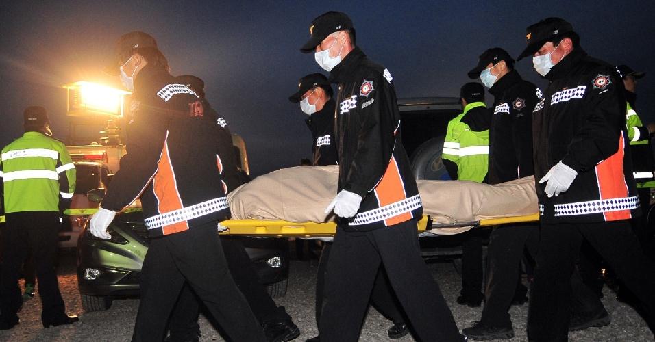 20.abr.2014 - Membros de uma equipe de resgate retiram o corpo de uma das 16 pessoas encontradas, neste domingo (20), na balsa que naufragou na quarta-feira (16) com 476 pessoas a bordo, na Coreia do Sul.