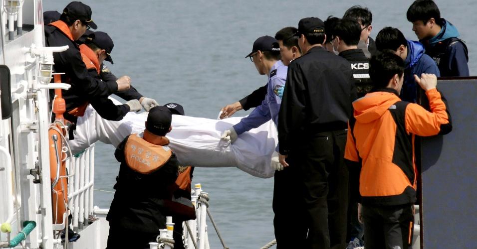 20.abr.2014 - Policiais carregam o corpo de vítima do naufrágio da balsa Sewol, ao chegarem ao porto de Jindo, sul da Coreia do Sul, neste domingo (20). Com o resgate de três novos corpos, há 49 mortos confirmados no acidente ocorrido com a embarcação que levava 476 pessoas, a maioria delas adolescentes alunos de uma escola, em viagem de campo. Apenas 179 foram resgatados com vida; mais de 200 continuam desaparecidos