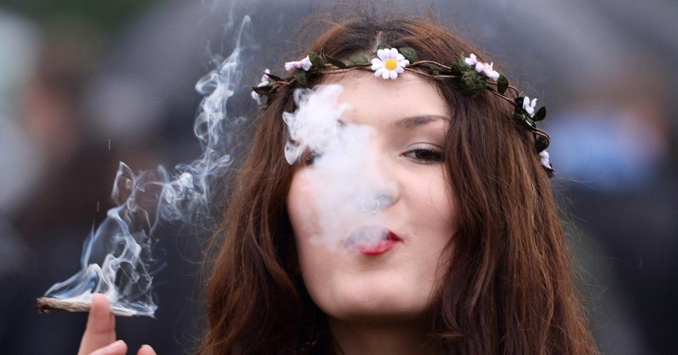 20.abr.2014 - Uma jovem fuma maconha durante uma manifestação pela legalização da droga, no Hyde Park, em Londres, neste domingo (20). Chamada de Dia 420, a marcha começou originalmente nos EUA, mas tem sido organizada em diversas cidades do mundo