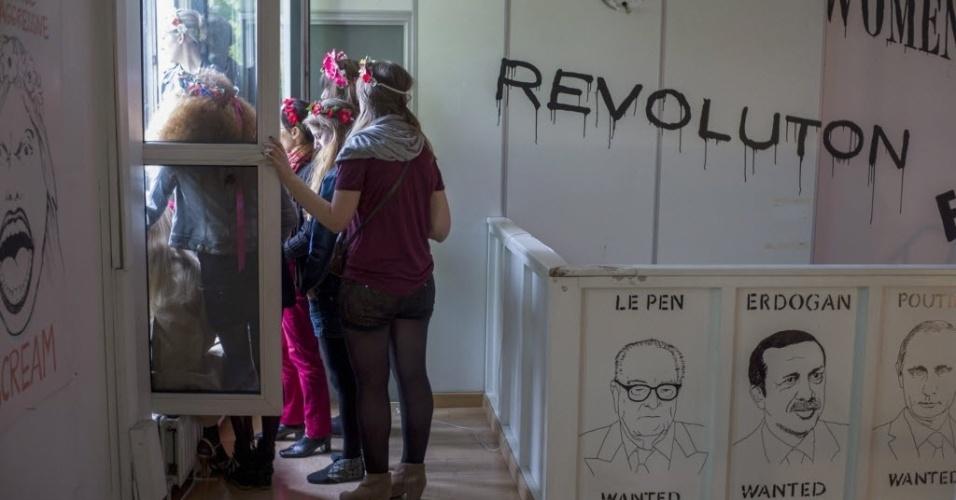 Ativistas do Femen olham pela janela da nova sede do grupo feminista em Clichy, perto de Paris (França), enquanto participam da festa de inauguração. A polícia decidiu na véspera aumentar a segurança na região, uma vez que grupos de extrema direita eram esperados no local