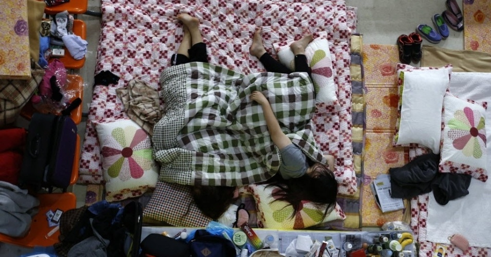 """21.abr.2014 - Familiares de um passageiro que estava a bordo da balsa """"Sewol"""", naufragada na quarta-feira (16), descansam enquanto esperam por notícias das equipes de resgate, em um alojamento improvisado na cidade portuária de Jindo, na Coreia do Sul, nesta segunda-feira (21)"""