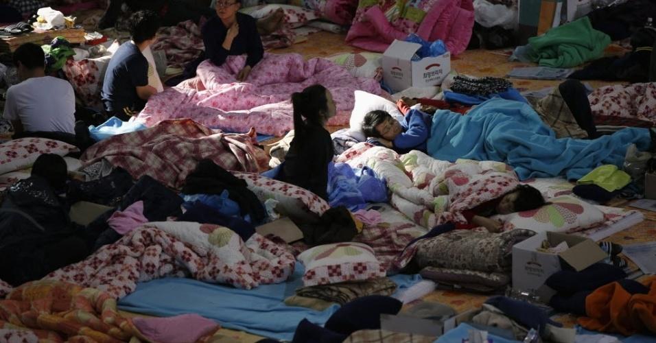 21.abr.2014 - Familiares dos passageiros que estavam a bordo da balsa que naufragou na Coreia do Sul, descansam enquanto esperam por notícias das equipes de resgate, em uma acomodação improvisada em um ginásio na cidade portuária de Jindo, nesta segunda-feira (21). O presidente da Coreia do Sul, Geun-hye, comparou ações de alguns tripulantes com assassinato