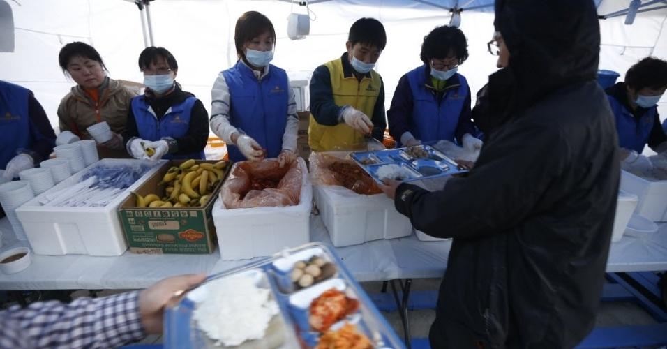 """21.abr.2014 - Voluntários distribuem alimentos para familiares dos passageiros desaparecidos a bordo da balsa """"Sewol"""", que naufragou na Coreia do Sul na quarta-feira (16), e esperam notícias dos parentes em Jindo, nesta segunda-feira (21). A presidente do país, Park Geun-hye, criticou a ação da tripulação da balsa que naufragou na quarta-feira (16) dizendo que ela foi """"semelhante a de um assassinato"""""""