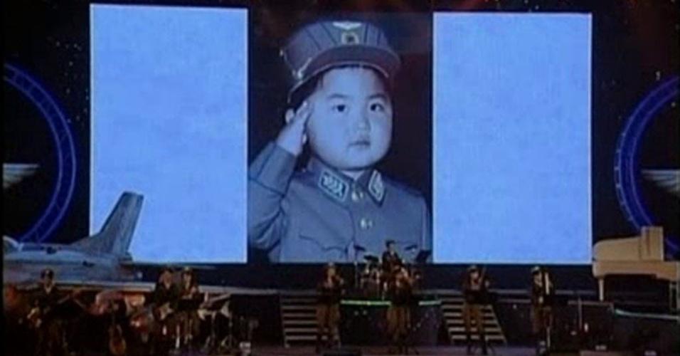 22.abr.2014 - Imagem tirada de vídeo divulgado pela emissora de televisão estatal da Coreia do Norte, nessa segunda-feira (21), mostra fotos do líder norte-coreano, Kim Jong-un, quando era criança, durante o concerto Moranbong, em Pyongyang, ocorrido no dia 16, segundo agência estatal. No final do concerto, uma tela gigante mostrou um documentário cronológico da dinastia Kim, contendo três fotos da infância de Kim Jong-um. Duas das fotos mostram Kim com aproximadamente quatro ou cinco anos, com um uniforme da força aérea, e a outra imagem mostra Kim mais velho em uma cabine de piloto. As fotos não puderam ser independentemente verificadas