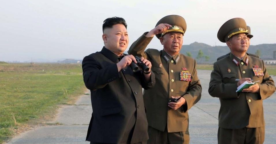 22.abr.2014 - O líder norte-coreano Kim Jong-un (à esq.), segurando um par de binóculos, participou de uma inspeção ao treinamento da Força Aérea do Exército da Coreia do Norte, nesta segunda-feira (21). A foto foi divulgada hoje pela agência oficial de notícias do país, sem revelar onde aconteceu a prática militar