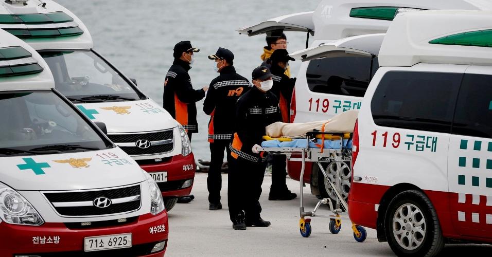 22.abr.2014 - Trabalhadores de serviços de emergência colocar corpo recuperado da balsa Sewol, naufragada na costa da Coreia do Sul, em ambulância no porto de Jindo, nesta terça-feira (22) Segundo um membro da tripulação do barco sul-coreano que afundou com 476 pessoas a bordo, os oficiais da ponte de comando foram repetidas vezes questionados se deveriam ou não dar ordem de abandonar o navio, mas não houve resposta. As autoridades confirmaram a morte de mais de cem pessoas no naufrágio