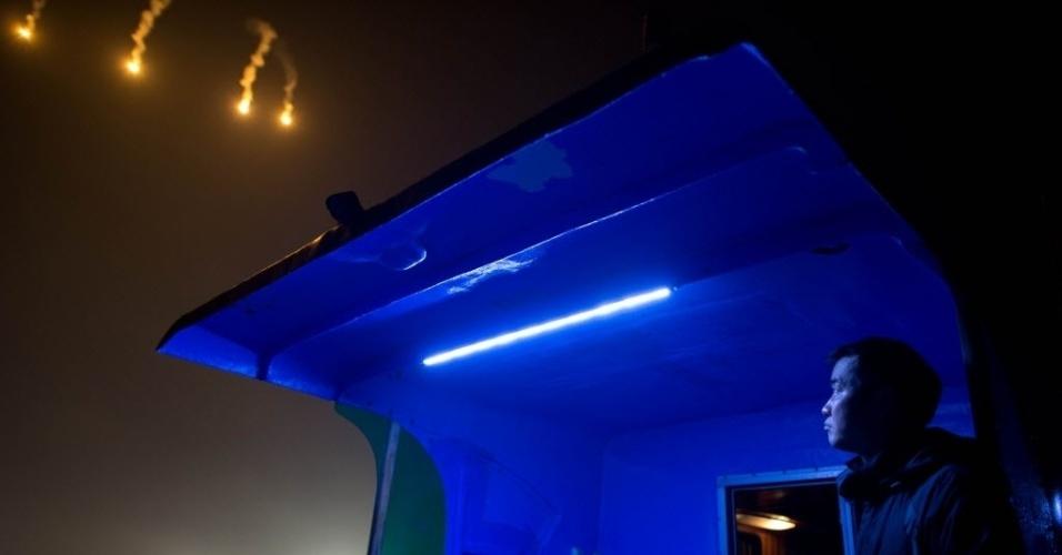 22.abr.2014 - Um jornalista observa sinalizadores lançados por equipes de busca e resgate durante as operações no local onde a balsa Sewol naufragou, na costa da ilha de Jindo, na Coreia do Sul, nesta terça-feira (22). Mergulhadores começaram a localizar os corpos dos passageiros e tripulantes que estavam a bordo da embarcação. O capitão foi preso e continua defendendo a sua decisão de atrasar a evacuação do barco quando ele começou a naufragar, com 476 pessoas a bordo