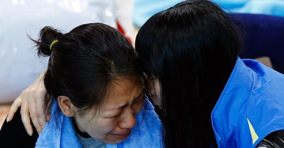 23.abr.2014 - Familiares de passageiros desaparecidos após o naufrágio da balsa sul-coreana Sewol se consolam no alojamento improvisado em um ginásio da cidade portuária de Jindo