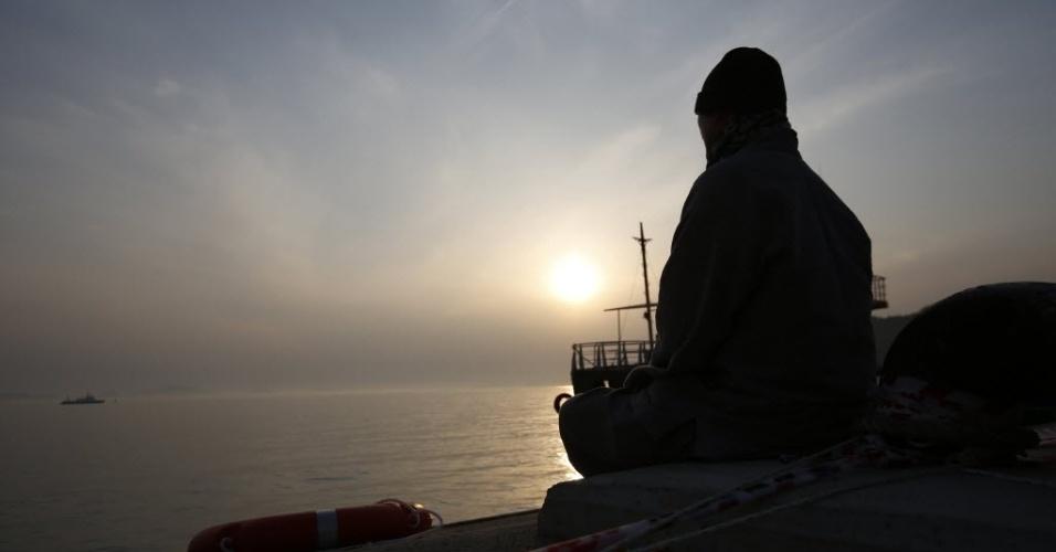 23.abr.2014 - Monge budista observa o mar enquanto reza pelos passageiros desaparecidos da balsa que naufragou na Coreia do Sul, em um porto onde familiares estão reunidos a espera de notícias das equipes de resgate, durante o pôr do sol em Jindo