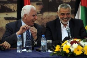 O chefe da delegação palestina, Azzam al-Ahmed (e), ao lado do primeiro-ministro do Hamas na faixa de Gaza, Ismail Haniya (c), durante entrevista em Gaza na quarta