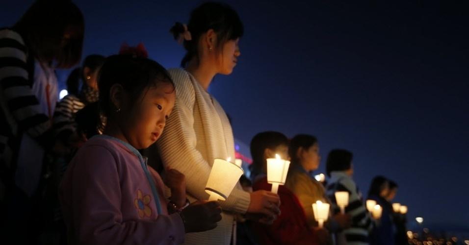 23.abr.2014 - Pessoas fazem uma vigília à luz de velas em Ansan para homenagear as vítimas da balsa que naufragou na Coreia do Sul, nesta quarta-feira (23)