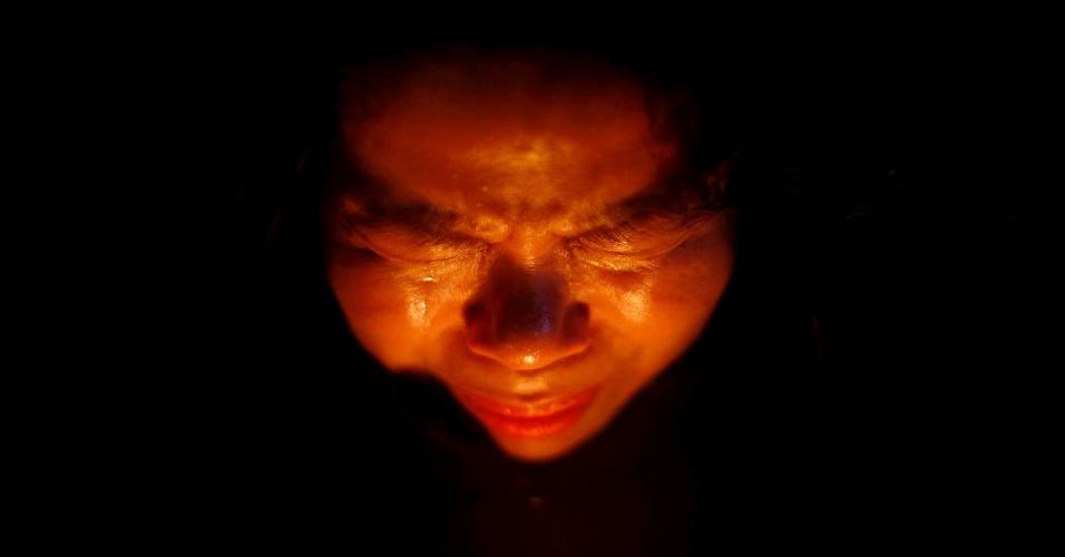 23.abr.2014 - Mulher chora enquanto reza durante uma vigília para as vítimas do naufrágio de Sewol, em Ansan, na Coreia do Sul, nesta quarta-feira (23)