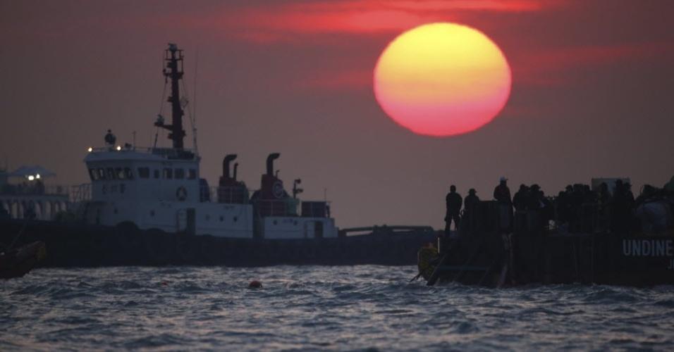 24.abr.2014 - Equipes de busca trabalham ao por do sol perto do ponto onde a balsa Sewol afundou na Coreia do Sul, no dia 16 de abril. A embarcação transportava 476 pessoas, e mais de 300 pessoas continuam desaparecidas. Nesta quinta-feira (24), o número de mortos subiu para 171. As investigações sobre o acidente estão centradas em falha humana ou mecânica