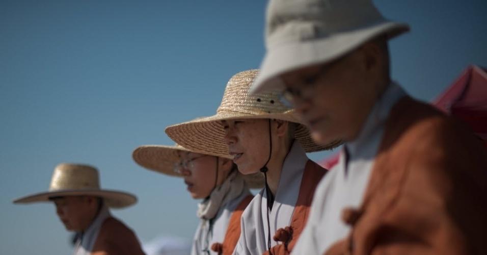 24.abr.2014 - Monges fazem orações pelas vítimas do naufrágio da balsa Sewol, que deixou mais de 300 mortos e desaparecidos na Coreia do Sul. Nesta quinta-feira (24), 11 dos 15 membros resgatados da tripulação foram acusados de homicídio por negligência e violação das leis marítimas