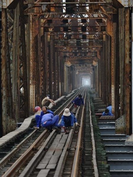24.abr.2014 - Operários fazem a manutenção nos trilhos da centenária ponte Long Bien (antiga Paul Doumer) em Hanói (Vietnã). Construída sob domínio francês no século 19, a estrada de ferro não teve muitos investimentos desde então. O transporte ferroviário é constantemente criticado no país - Hoang Dinh Nam/AFP