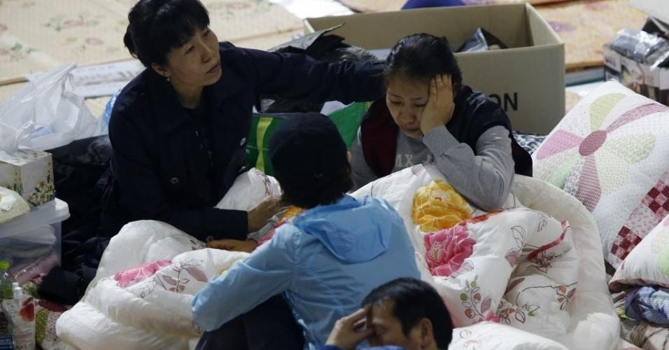 26.abr.2014 - Familiares de passageiros desaparecidos a bordo balsa Sewol, em 16 de abril, descansam em um alojamento improvisado em um ginásio em Jindo, neste sábado (26), enquanto esperam por notícias das equipes de busca e salvamento