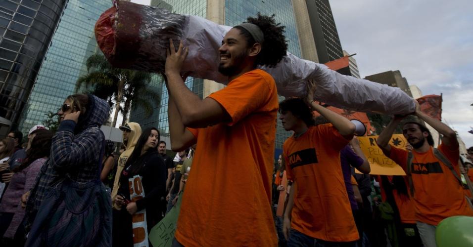 26.abr.2014 - Grupo carrega um cigarro falso de maconha gigante durante a Marcha da Maconha de São Paulo, neste sábado. Este ano o evento defende o cultivo caseiro da erva