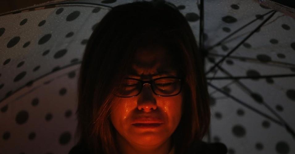 27.abr.2014 - Coreana chora durante vigília à luz de velas em homenagem às vítimas do naufrágio da balsa Sewol, neste domingo (27). As orações também são destinadas aos desaparecidos no incidente. O primeiro-ministro sul-coreano, Chung Hong-won, renunciou após receber críticas pela gestão da tragédia ocorrida em 16 de abril