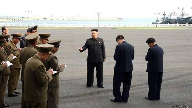28.abr.2014 - Fotografias divulgadas recentemente do líder norte-coreano Kim Jong-un chamaram a atenção por um detalhe em comum: em todas as fotos, ele aparece rodeado por oficiais e generais fazendo anotações em cadernos. As imagens foram publicadas pela Agência de Notícias Central (KCNA) no país e mostram Kim Jong-un caminhando em um porto pesqueiro, conversando com um piloto que faz um voo de treinamento e inspecionando as instalações de um acampamento juvenil reformado. E quem são aqueles homens fazendo tantas anotações? Eles não são jornalistas, e sim soldados, membros do partido ou funcionários do governo, que registram até as piadas feitas pelo líder