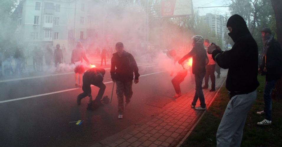 28.abr.2014 - Militantes pró-Rússia acendem sinalizadores enquanto participam de um ataque a manifestantes pró-Ucrânia em Donetsk, nesta segunda-feira (28). Separatistas agrediram com tacos de beisebol e barras de ferro quem participava de uma marcha em favor da unidade do país, segundo presenciou um jornalista da agência de notícias AFP. Várias pessoas ficaram feridas