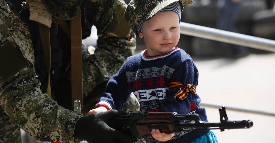 28.abr.2014 - Um menino segura a arma de um separatista pró-Rússia na cidade de Kostyantynivka, no leste da Ucrânia, nesta segunda-feira (28). Rebeldes tomaram o controle da sede da polícia e de um prédio da administração da cidade, segundo um porta-voz do governo da região
