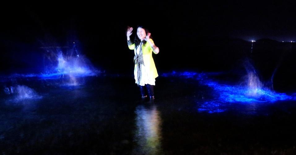 28.abr.2014 - Chinesa posa cercada pelo brilho azulado de flagelados (Flagellata) na praia de Dalian, nordeste da China, na segunda-feira (28). Uma grande quantidade destes organismos unicelulares foi observada no mar da região por dias, e eles emitem luz em tons azuis quando a água é agitada