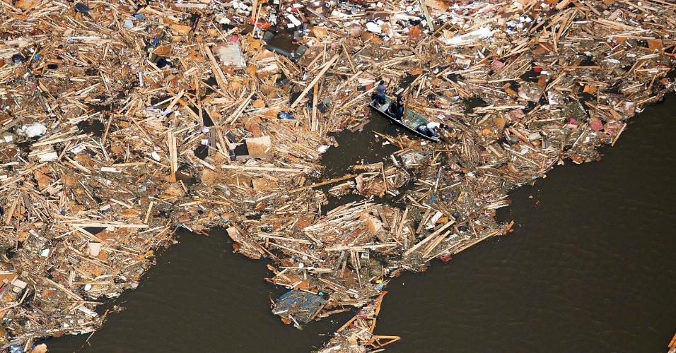 28.abr.2014 - Homens em barco usam placas de madeira como pás, ao buscar escombros de casas em lago, depois que um tornado atingiu a cidade de Vilonia, Arkansas, no centro-sul dos EUA, nesta segunda-feira (28). Uma onda de tornados atingiu a região central do país, matando pelo menos 18 pessoas no Estados de Arkansas, Oklahoma e Iowa